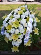Wiązanka pogrzebowa z kwiatów żywych, wielkość: duża, lilia kremowa, chryzantema gałązkowa biała, róża kremowa (Avalanche), zieleń dekoracyjna, podkład jodłowy, szarfa jedwabna szer. 7 cm druk cyfrowy (+20 zł).