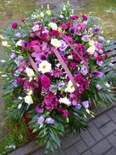 Wiązanka pogrzebowa z kwiatów żywych, eustomy fioletowe i kremowe, storczyki ciemnoróżowe, cantadeschie cielnoróżowe, chryzantema gałązkowa bordowa, goździki gałązkowe bordowe, liście chico, zieleń dekoracyjna, kokarda bordowa.