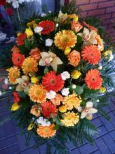 Wiązanka pogrzebowa z kwiatów żywych, gerbery, róże, storczyki, tulipany i goździki w ciepłych odcieniach herbaciano-żółtych.