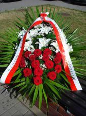 Wiązanka pogrzebowa z żywych kwiatów, wielkość: duża, lilie białe, róże czerwone, zieleń dekoracyjna, liść palmy, podkład jodłowy, szarfa PP szer. 8 cm (+20 zł).