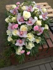 Wiązanka pogrzebowa z kwiatów żywych, średniej wielkości zagęszczona, róże kremowe, storczyki jasnoróżowe i goździki gałązkowe pudrowy róż, obwód liść chico.