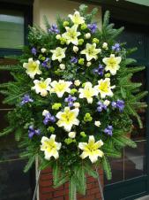 Wieniec pogrzebowy z żywych kwiatów, kształt nieregularny, brak liści tła, lilie kremowe (Conca D'or), irysy fioletowe, chryzantema zielona (Santini), podkład jodłowy, zieleń dekoracyjna.