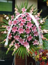 Wieniec pogrzebowy z żywych kwiatów, kształt okrągły, lilie różowe (Sorbona), mieczyki różowe, liście palmy, podkład jodłowy, zieleń dekoracyjna, szarfa satynowa 7cm, druk komputerowy (+20 zł).