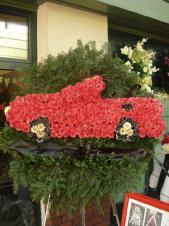Wieniec pogrzebowy z żywych kwiatów, w kształcie samochodu, chryzantemy kolor, liście kordyliny, bukszpan, podkład jodłowy, zieleń dekoracyjna.