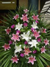 Wieniec jednopłaszczyznowy, lilia różowa i biała, storczyk fioletowy (Phalaenopsis), zieleń dekoracyjna, liść palmy, podkład jodłowy.