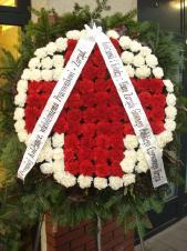 Wieniec w kształcie koła, goździk czerwony i biały, zieleń dekoracyjna, podkład jodłowy, szarfa satynowa szer. 10 cm (+30 zł).