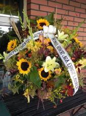 Kosz pogrzebowy z kwiatów żywych, słoneczniki żółte, lilie kremowe, storczyki złote, wypełnienie zielenią dekoracyjną, gąbka florystyczna w koszu wiklinowym, szarfa taśma plastikowa 8cm, napis ręczny (obecnie niedostępna).