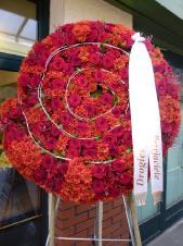 Wieniec nietypowy w kształcie amonitu, wielkość: ok. 1,2 m, magrarytka herbaciana, róża czerwona (Red Naomi), rattan dekoracyjny, zieleń dekoracyjna, szarfa satynowa szer. 7 cm (+20 zł).