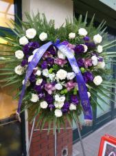 Wieniec pogrzebowy z żywych kwiatów, kształt serca, róże kremowe (Avalanche), eustoma fioletowa, storczyk różowy (Cymbidium), zielona chryzantema gałązkowa (Santini), podkład jodłowy, zieleń dekoracyjna, liść palmowy, szarfa satynowa w kolorze fioletowym szr. 7 cm (+30 zł).