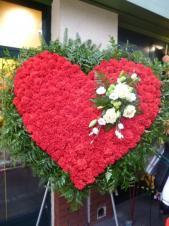 Wieniec pogrzebowy z żywych kwiatów, kształt serca z broszą, czerwone goździki, róża biała, eustoma biała, liście paproci, podkład jodłowy.