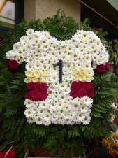 Wieniec pogrzebowy - koszulka Mistrza Polski, chryzantemy gałązkowe białe, róże czerwone i białe, podkład jodłowy, liście paproci.