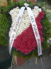Wieniec pogrzebowy z kwiatów żywych, herb klubu sportowego, chryzantemy gałązkowe białe, czerwone i czarne, podkład jodłowy, liście paproci, szarfa satynowa 7cm. szer.