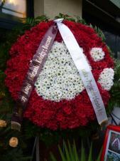 Wieniec pogrzebowy z żywych kwiatów, logo restauracji, chryzantema gałązkowa biała i czerwona, liście paproci, podkład jodłowy, szarfa satynowa 10 cm. szer. połowa kolorowa.