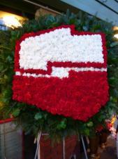 Wieniec nietypowy w kształcie logo, wielkość: ok. 1,2 m, goździki białe i czerwone, chryzantemy białe, zieleń dekoracyjna.