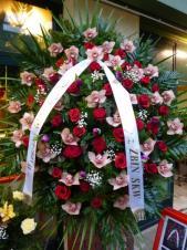 Wieniec owalny jednopłaszczyznowy, bardzo duży, róże pąsowe, storczyki różowe, tulipany fioletowe, liść palmy, zieleń dekoracyjna.