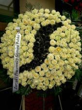 Wieniec pogrzebowy okrągły, średnica: ok. 100 cm., kremowe róże z malowanym logo w kolorze czarnym, podkład jodłowy, zieleń dekoracyjna.