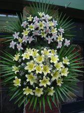 Wieniec pogrzebowy z żywych kwiatów, wielkość: bardzo duży, storczyki białe (Cymbidium), lilie kremowe (Conca d'Or), liść palmy, podkład jodłowy, zieleń dekoracyjna.
