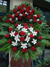 Wieniec z żywych kwiatów, wielkość: duży, róże pąsowe, storczyki białe (Cymbidium), liść palmy, paproć leśna, paproć drzewiasta, podkład jodłowy, zieleń dekoracyjna.