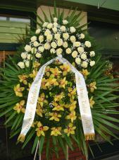 Wieniec z żywych kwiatów, wielkość: bardzo duży, róże kremowe (Avalanche), storczyki złote, chryzantema zielona (Santini), liść palmy, podkład jodłowy, zieleń dekoracyjna, szarfa satynowa 10cm, druk komputerowy.