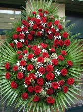 Wieniec z żywych kwiatów, wielkość: bardzo duży, róże pąsowe, liście palmy, podkład jodłowy, zieleń dekoracyjna, wieniec z wyraźnie zaznaczoną przypinką (wypukłością) w górnej części.