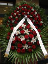 Wieniec z żywych kwiatów, wielkość: bardzo duży, róże pąsowe, storczyki białe, liść palmy, paproć drzewiasta, liść palmy, podkład jodłowy, szarfa satynowa 8cm, druk komputerowy.