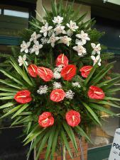 Wieniec z żywych kwiatów, wielkość: średni, storczyki białe (Cymbidium), anthurium czerwone, liść palmy, podkład jodłowy, zieleń dekoracyjna.