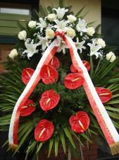 Wieniec pogrzebowy z kwiatów żywych, anthurium czerwone, róże kremowe (Avalanche), lilie białe (Casablanca), liść palmy, podkład jodłowy, zieleń dekoracyjna, szarfa satynowa biało-czerwona 10cm, druk komputerowy.