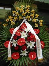 Wieniec z żywych kwiatów, wielkość: bardzo duży, lilie białe (Syberia), storczyki złote (Cymbidium), anthurium czerwone, róże pąsowe, liść palmy, podkład jodłowy, zieleń dekoracyjna, szarfa satynowa 10cm, druk komputerowy.