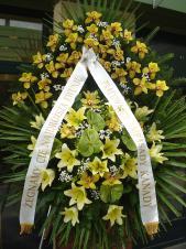 Wieniec z żywych kwiatów, wielkość: bardzo duży, lilie kremowe (Conca D'Or), storczyki złote (Cymbidium), anthurium zielone (Midori), liść palmy, podkład jodłowy, zieleń dekoracyjna, szarfa satynowa 10cm, druk komputerowy.