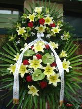 Wieniec z żywych kwiatów, wielkość: duży, lilie kremowe (Conca D'Or), róże pąsowe, storczyki zielone, anthurium zielone (Midori), liść palmy, podkład jodłowy, zieleń dekoracyjna, szarfa satynowa 7cm, druk komputerowy.