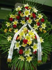 Wieniec z żywych kwiatów, wielkość: bardzo duży, lilie kremowe (Conca D'Or), storczyki złote (Cymbidium), róże pąsowe, liść palmy, podkład jodłowy, zieleń dekoracyjna, szarfa satynowa 7cm, druk komputerowy.