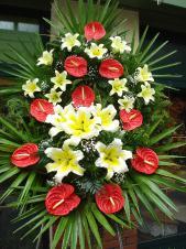 Wieniec z żywych kwiatów, wielkość: duży, lilie kremowe (Conca D'Or), anthurium czerwone, liść palmy, podkład jodłowy, zieleń dekoracyjna.