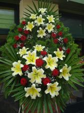 Wieniec z żywych kwiatów, wielkość: duży, róże pąsowe, lilie kremowe (Conca D'Or), liść palmowy, podkład jodłowy, zieleń dekoracyjna.