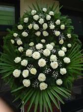 Wieniec z żywych kwiatów, wielkość: średni, róże kremowe (Avalanche), liść palmy, podkład jodłowy, zieleń dekoracyjna.