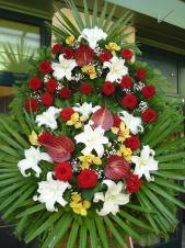 Wieniec z żywych kwiatów, wielkość: duży, róże pąsowe, storczyki złote (Cymbidium), lilie białe (Casablanca), anthurium bordowe (Safari), liść palmy, podkłąd jodłowy, zieleń dekoracyjna.