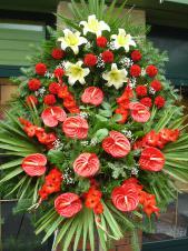 Wieniec z żywych kwiatów, wielkość: duży, lilie kremowe (Conca D'Or), goździki czerwone, anthurium czerwone, mieczyki czerwone, liść palmy, podkład jodłowy, zieleń dekoracyjna.
