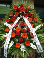 Wieniec z żywych kwiatów, wielkość: duży, gerbery czerwone, róże pąsowe, mieczyk biały, liść palmy, podkład jodłowy, zieleń dekoracyjna, szarfa taśma plastikowa 8cm, napis ręczny.