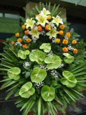 Wieniec z żywych kwiatów, wielkość: średni, lilie kremowe (Conca D'Or), róże herbaciane, anthurium zielone (Midori), liść palmy, podkład jodłowy, zieleń dekoracyjna.