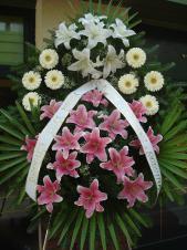 Wieniec z żywych kwiatów, wielkość: średni, lilie białe (Casablanca), gerbery białe, lilie różowe (Sorbona), liść palmy, podkład jodłowy, zieleń dekoracyjna, szarfa taśma palstikowa, pismo ręczne.