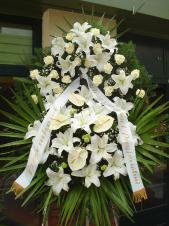 Wieniec pogrzebowy z żywych kwiatów, wielkość: duży, lilie białe (Casablanca), anthurium białe (Presence), róże kremowe (Avalanche), chryzantema zielona (Santini), liść palmy, podkład jodłowy, zieleń dekoracyjna, szarfa satynowa 10cm, druk komputerowy.