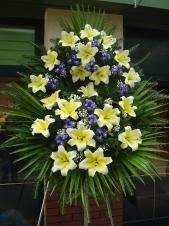 Wieniec pogrzebowy z żywych kwiatów, wielkość: średni, lilie kremowe, irysy fioletowe, liść palmy, podkład jodłowy, zieleń dekoracyjna.