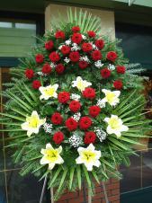 Wieniec pogrzebowy z żywych kwiatów, wielkość: duży, róże pąsowe, lilie kremowe, liście palmy, podkład jodłowy, zieleń dekoracyjna, szarfa taśma plastikowa 8cm, napis ręczny.