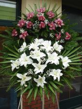 Wieniec pogrzebowy z żywych kwiatów, wielkość: średni, storczyki fioletowe, lilie białe, liść palmy, podkład jodłowy zieleń dekoracyjna.