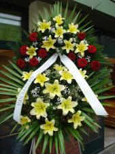 Wieniec pogrzebowy z żywych kwiatów, lilie kremowe (Conca d'Or), róże pąsowe, liść palmy, podkład jodłowy, zieleń dekoracyjna, szarfa taśma plastikowa 8cm, napis ręczny.