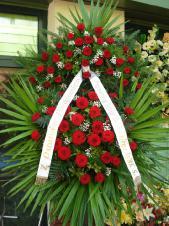 Wieniec pogrzebowy z kwiatów żywych, wielkość: duży, róże pąsowe, liść palmy, podkład jodłowy, zieleń dekoracyjna, szarfa satynowa 7cm, druk komputerowy.