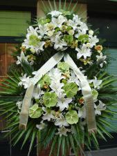 Wieniec pogrzebowy z kwiatów żywych, wielkość: bardzo duży, lilie białe (Casablanca), storczyki zielone (Cymbidium), anthurium zielone (Midori), róże białe (Akito), liść palmy, cykas, podkład jodłowy, zieleń dekoracyjna, szarfa satynowa kolor pistacja 10cm, druk komputerowy.