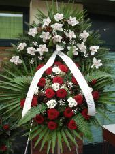Wieniec z żywych kwiatów, wielkość: duży, storczyki białe (Cymbidium), róże pąsowe, chryzantemy białe (Bacardi), liście palmy, podkład jodłowy, zieleń dekoracyjna.