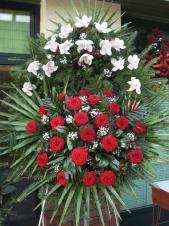 Wieniec pogrzebowy z żywych kwiatów, wielkość: średni, storczyki białe (Cymbidium), róże pąsowe, liście palmy, podkład jodłowy, zieleń dekoracyjna.