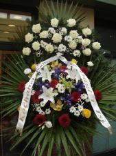 Wieniec z żywych kwiatów, wielkość: średni, róże kremowe(Avalnache), irysy fioletowe, lilie białe (Casablanca), róże pąsowe, margerytka biała (Bacardi), strorczyki złote (Cymbidium), eustoma biała, liść palmy, podkład jodłowy, zieleń dekoracyjna.