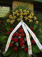 Wieniec z żywych kwiatów, wielkość: duży, róże pąsowe, storczyki złote (Cymbidium), liść palmy, liść kordyliny zielonej, podkład jodłowy, zieleń dekoracyjna, szarfa satynowa 7cm (podwójna) (+30zł)